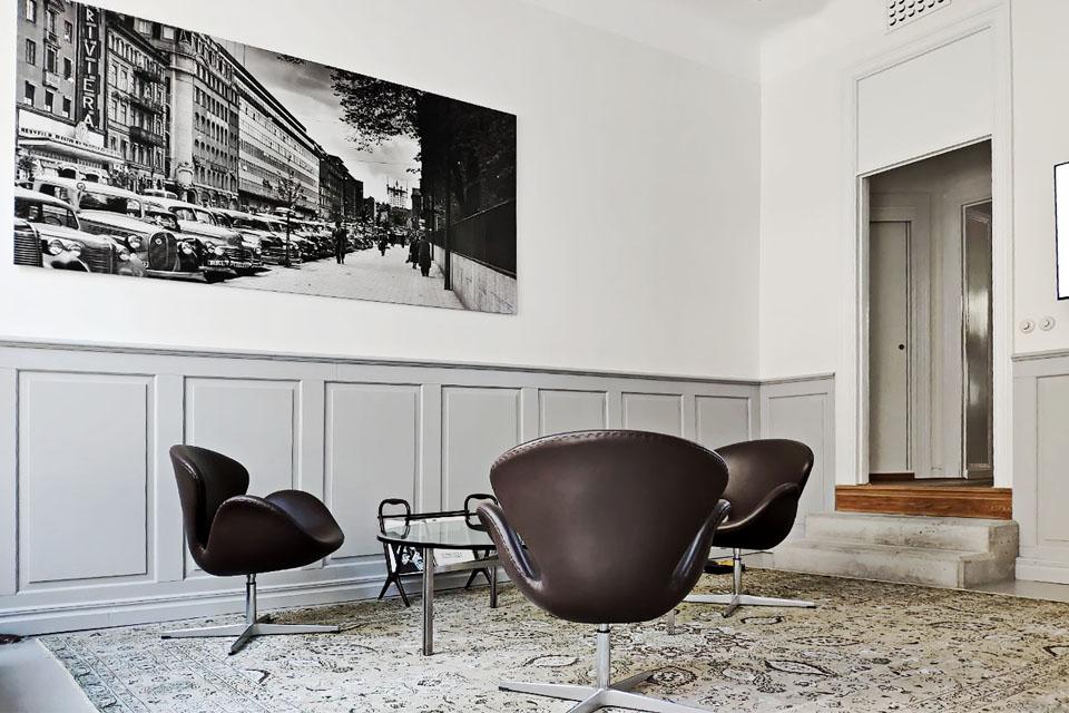 En bild från entren till showroomet. På bilden syns tre fotöljer, ett soffbord och en tavla över Stockholm.